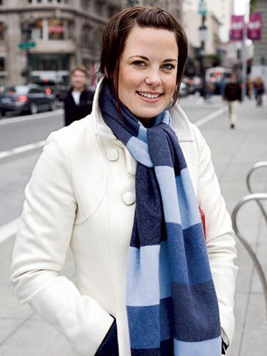 woman in a white coat and blue scarf standing on a san francisco street