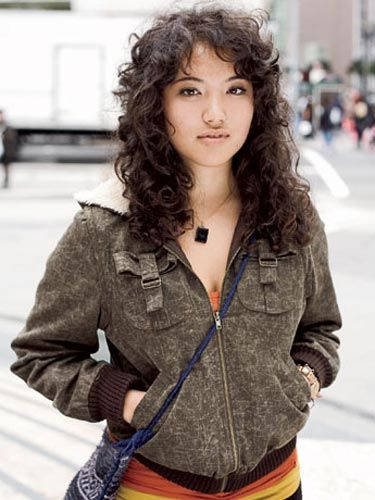 woman with curly hair standing on a san francisco street