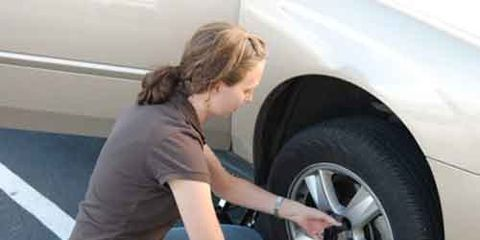 woman changing a flat tire