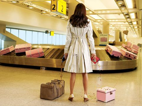 model in white trench in airport with baggage