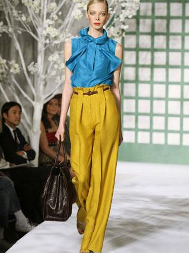 model on runway wearing yellow pants and blue top