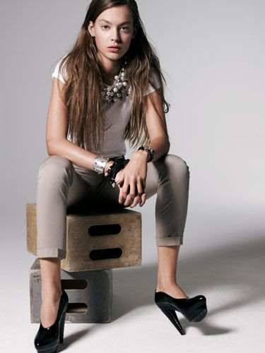 model in skinny pants and black heels sitting on crates