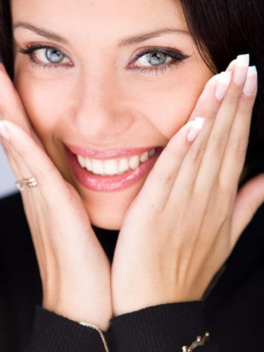 smiling woman with her hands to her face
