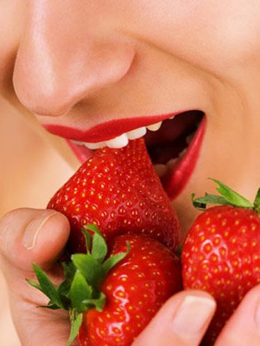 woman eating a handful of strawberries