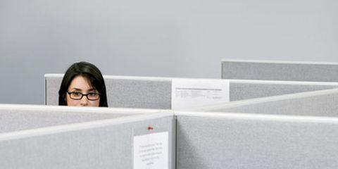 woman peering over cubicle