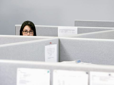 woman peering over cubicle