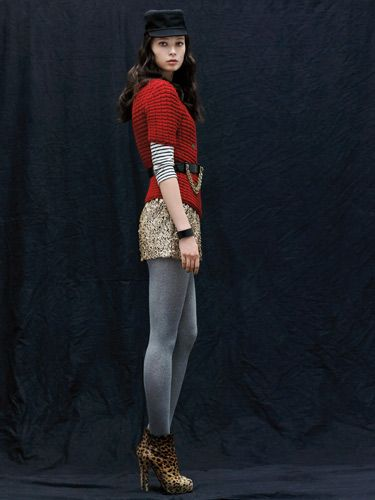 model in belted red sweater over gold sequin skirt gray tights and leopard print booties