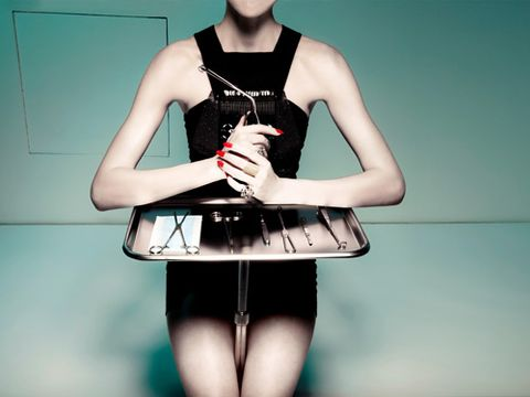 model with tray of plastic surgery tools