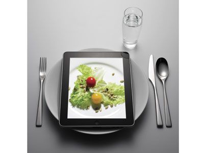 ipad with plate, silver ware, and water