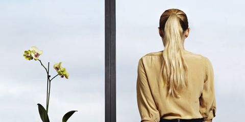 businesswoman sitting on desk looking out