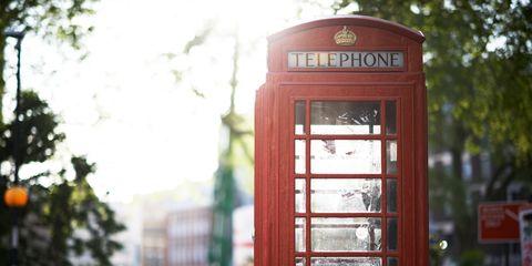 Telephone booth, Red, Payphone, Urban area, Tree, Telephone, Sunlight, City, Telephony, Plant,