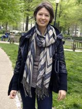 woman in black jacket and blue and cream scarf