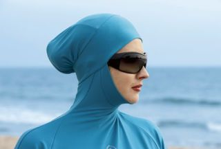 woman in blue burkini and sunglasses