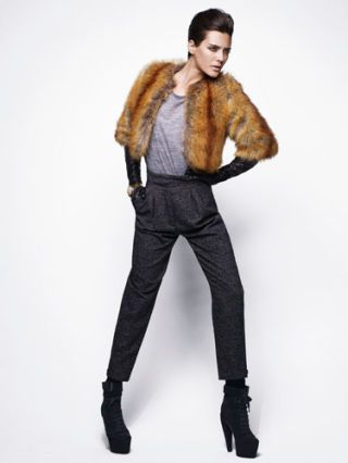 model in brown fur vest and black pants