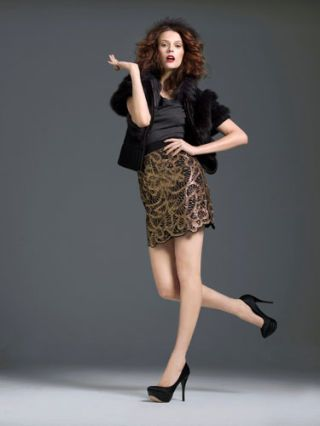 model in gold skirt and black faux fur cover up