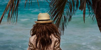model on the beach in tan jacket and hat