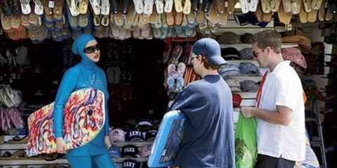 woman in blue burkini with boogie board guys