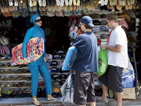 woman in blue burkini with boogie board guys
