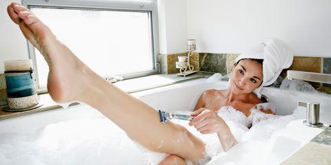 Woman in bathtub shaving her legs