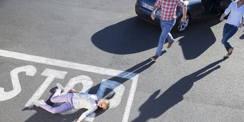 Woman lying in street after car accident emergency