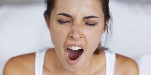 A woman yawning feeling tired