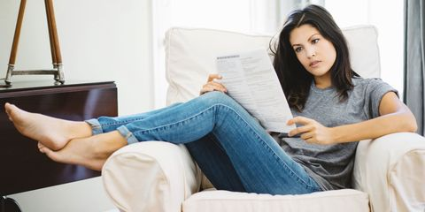 Woman reading letter on sofa in living room
