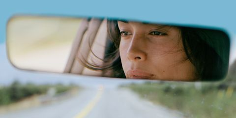 A woman driver that can be seen in her rear view mirror