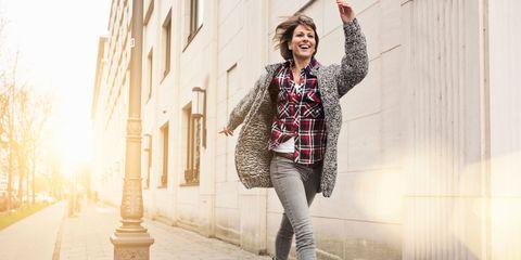 Energetic and happy woman walking down street