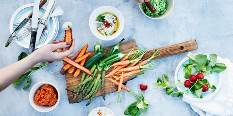 A table of health foods - carrots, asparagus, peppers.