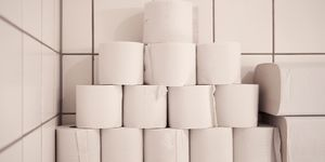 Pyramid of white toilet rolls resting in white tiled bathroom