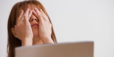 woman at computer screen rubbing eyes