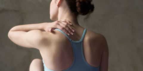 Woman massages her aching back after a workout
