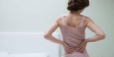 A young woman rubbing her aching back
