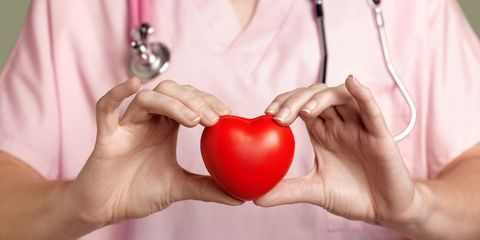 cardiologist in pink scrubs holding red heart