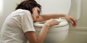 Sick young woman leaning on toilet bowl