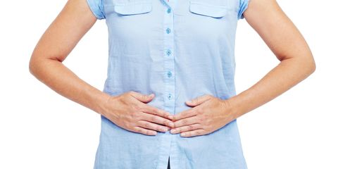 Cropped image of a woman pushing on her stomach with both hands - isolated on white