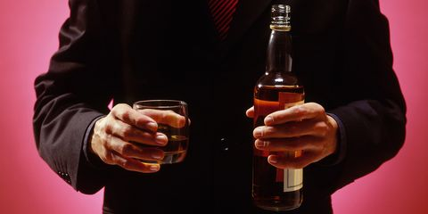 man holding whiskey glass and bottle