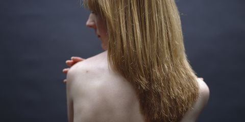 woman with bare back with hand on shoulder
