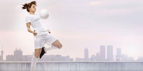Ball, Football, Sports equipment, Human leg, Soccer ball, Tower block, Ball, Playing sports, T-shirt, Cityscape,