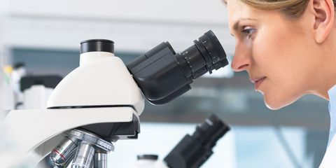 woman stares into a microscope