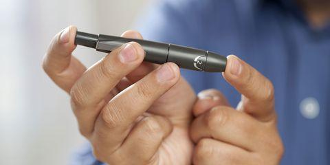 man pricking finger for glucose test