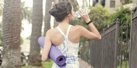 Woman walking drinking water holding yoga mat