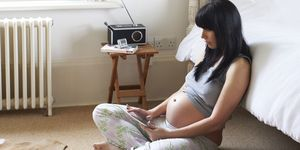 Pregnant woman leaning on bed on tablet