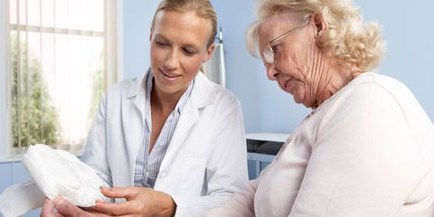 Doctor explain incontinence pads to elderly woman