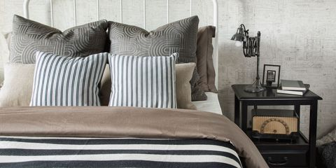 Bed with stripey bedspread and lots of pillow
