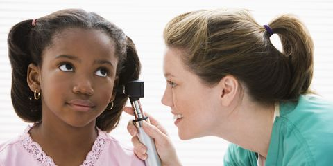 A doctor investigating a child's ear