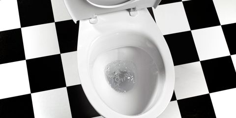 White toilet with seat up, black and white tiles underneath