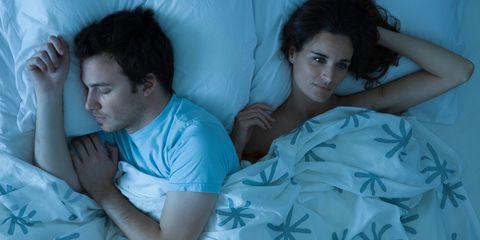 Couple in bed. Man sleeping; woman awake