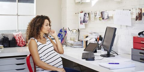 A pregnant woman in front of her computer