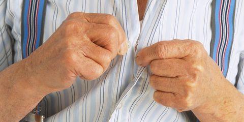 Elderly man buttoning up shirt